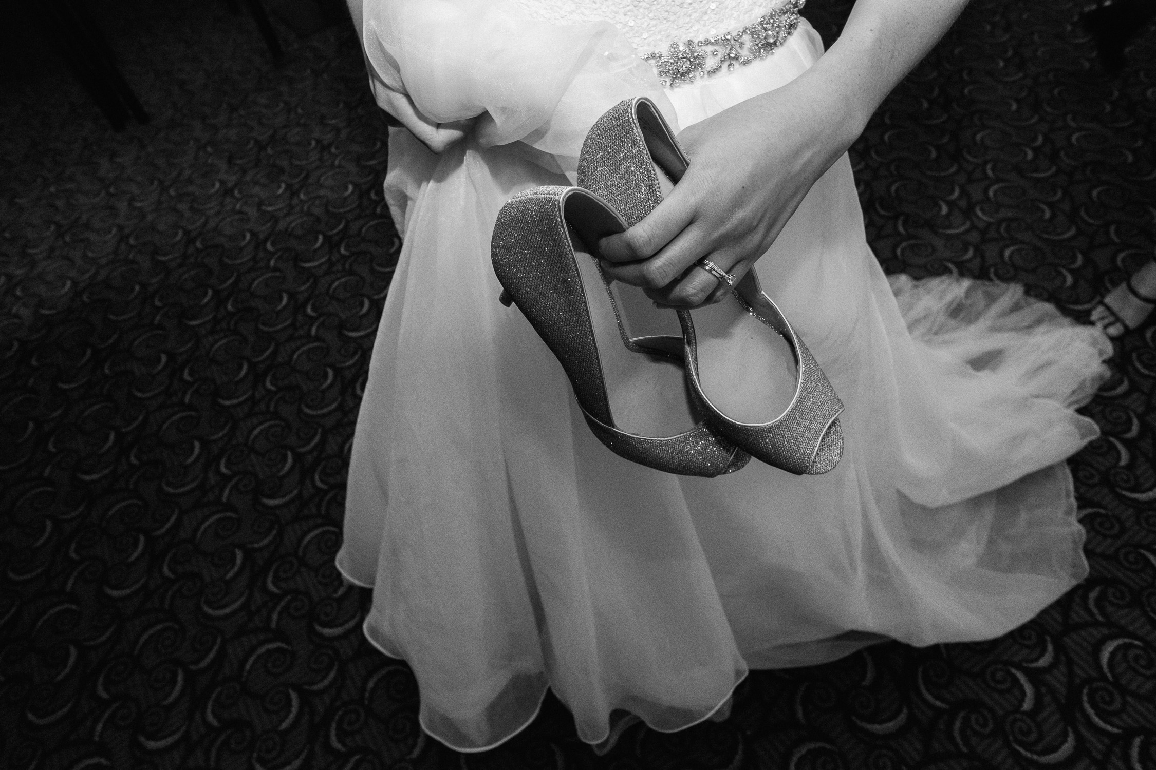 Lynsey and Kai's Melbourne wedding - bride holding her glittery high heeled shoes at wedding reception at the Marriott Hotel