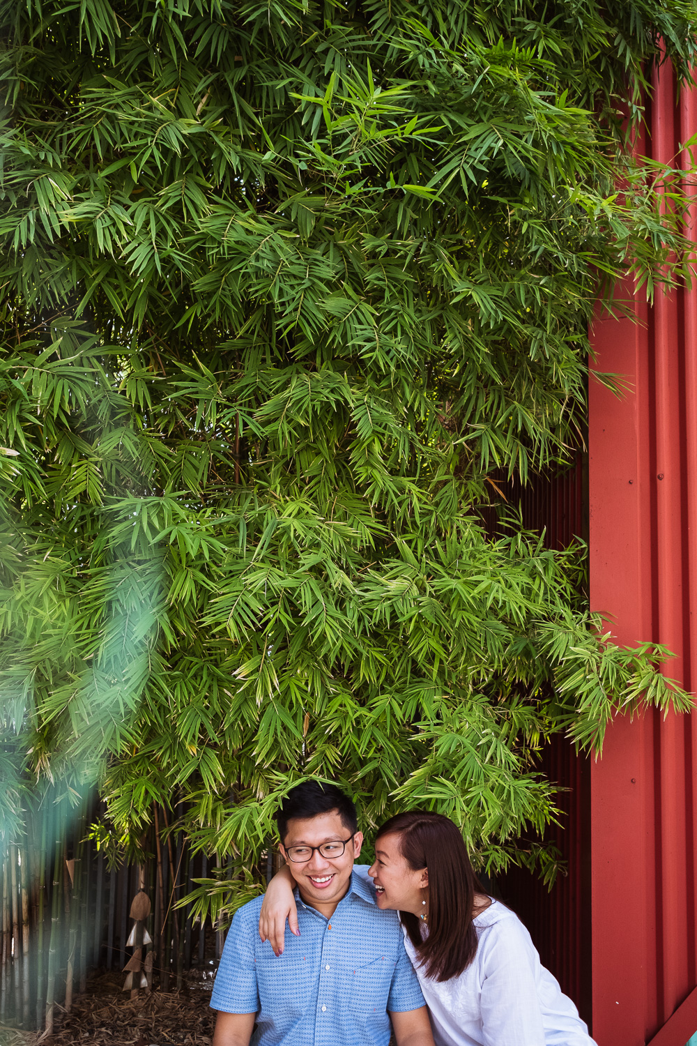 Couple standing under bamboo trees and red wall for prewedding shoot