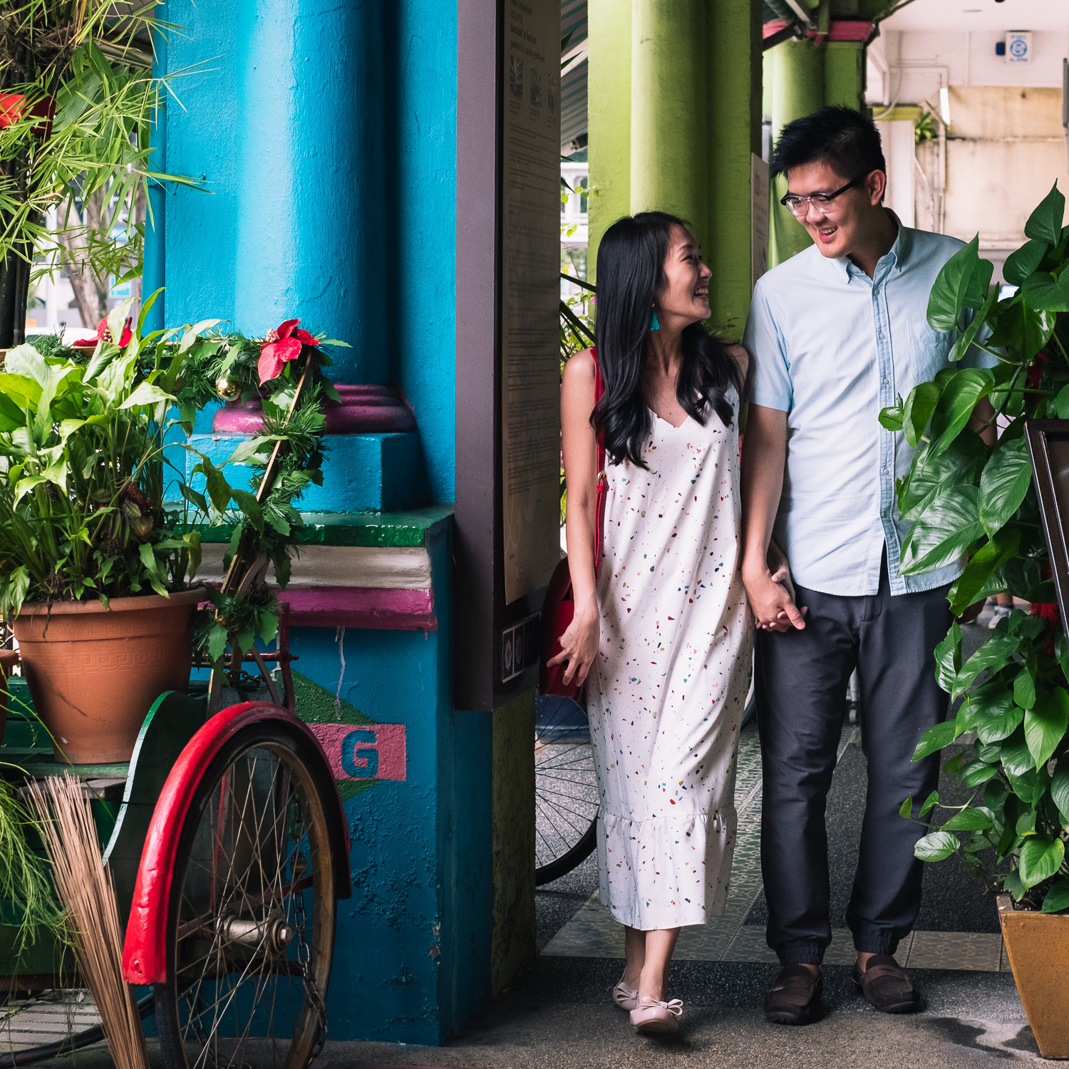 Asian couple with blue walls and plants in a red trishaw, Singapore prewedding shoot