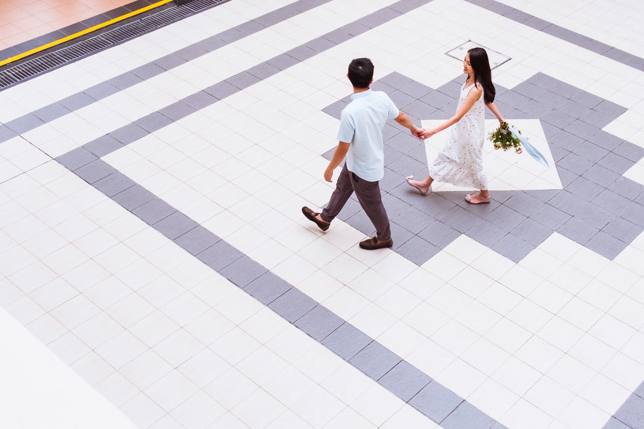 Engaged couple with bouquet walking across graphic tile floor