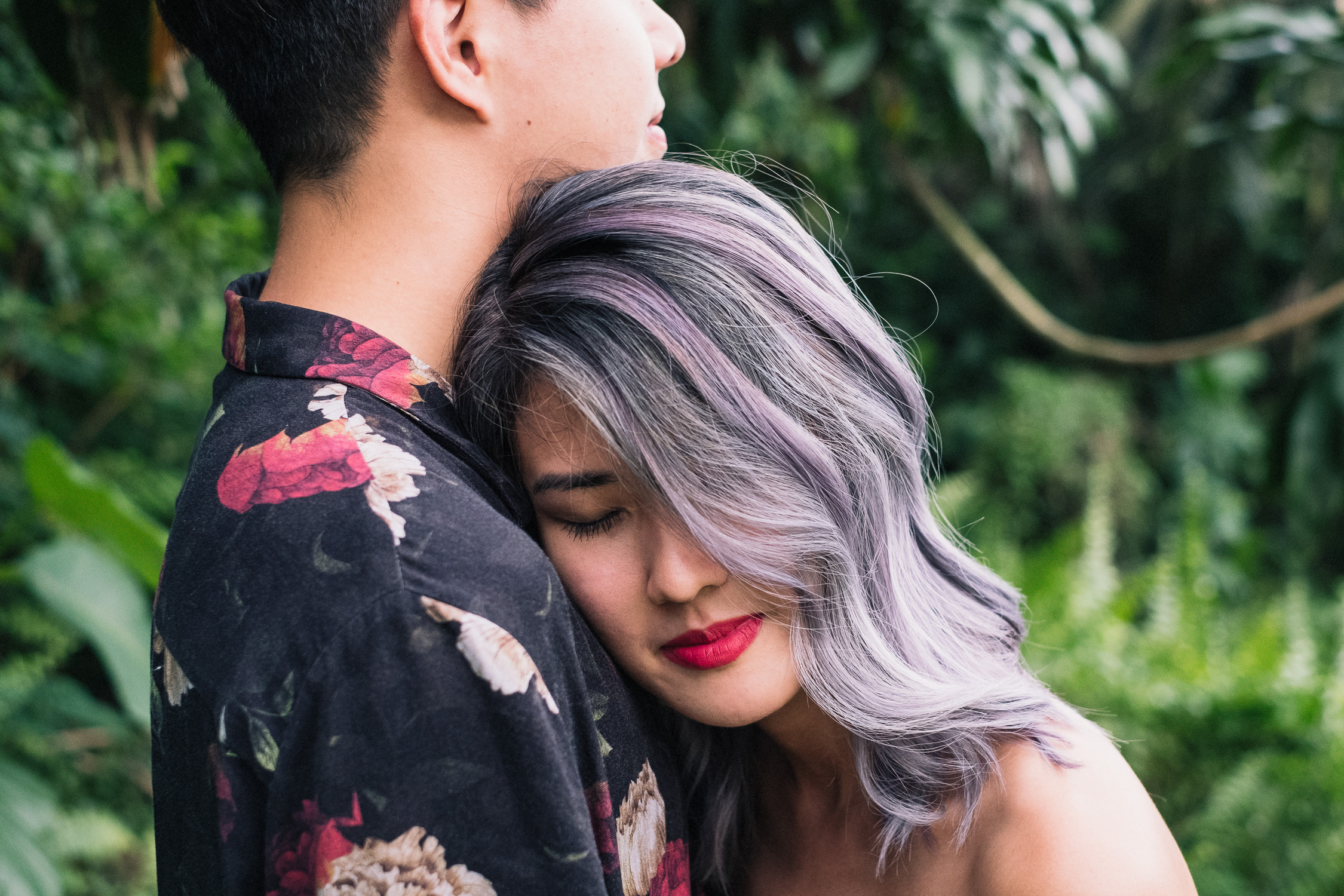 Suwan laying on Jean Francois chest from their Singapore prewedding forest shoot - purple hair floral shirt red lips