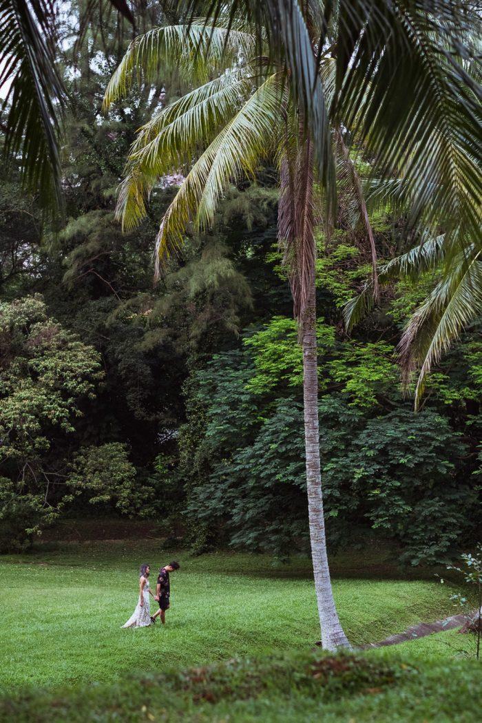 Suwan Jean Francois walking on in field with palm tree in Singapore prewedding forest shoot