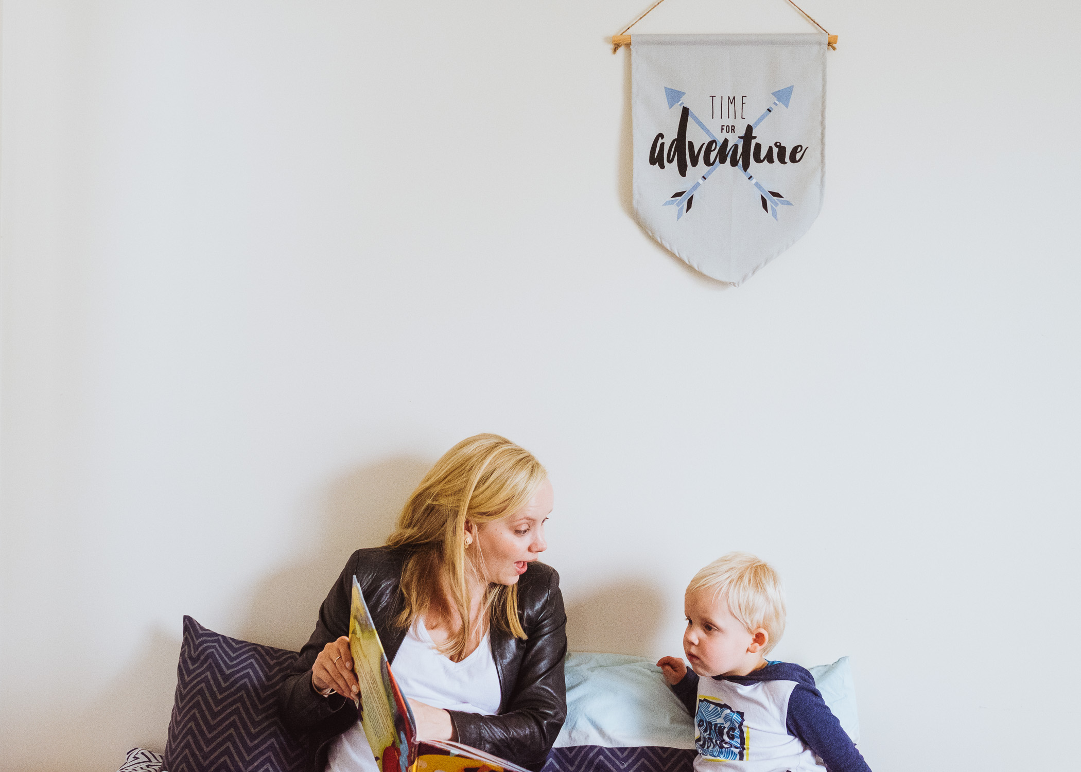 Day In The Life - mum and toddler reading under Adventure sign